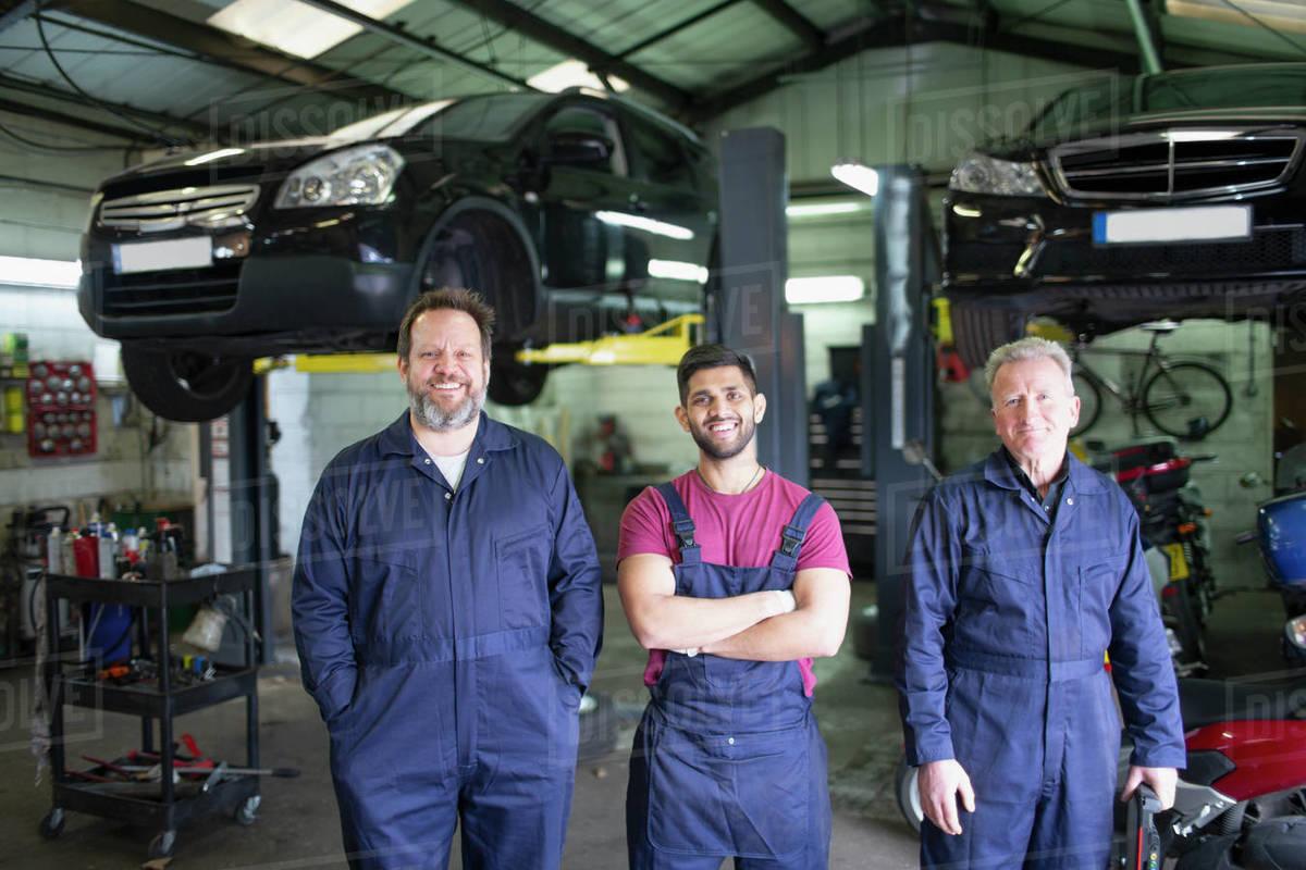 Portrait confident male mechanics in auto repair shop Royalty-free stock photo