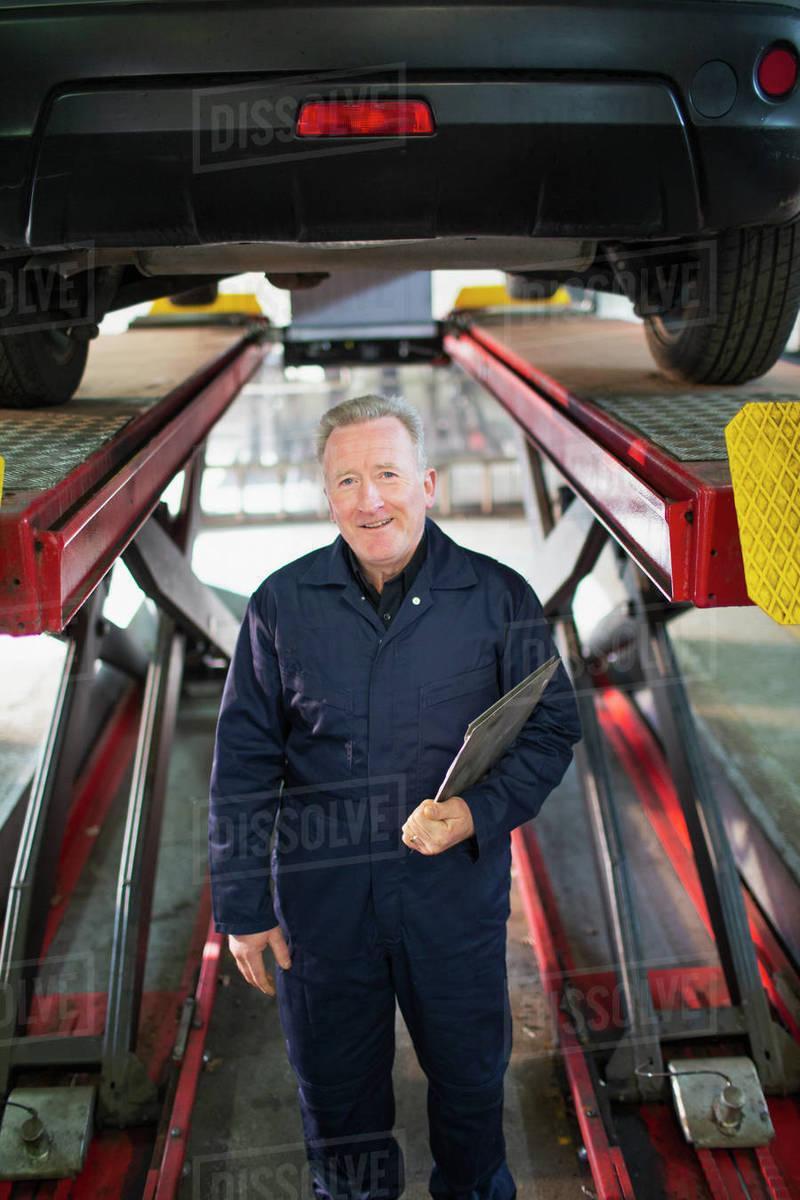 Portrait confident male mechanic under car in auto repair shop Royalty-free stock photo