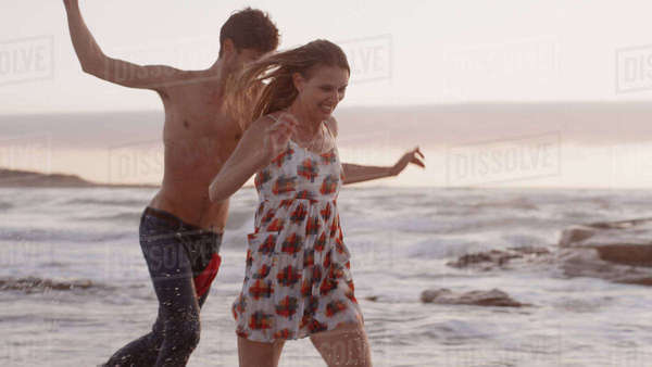 Playful young couple running on beach Royalty-free stock photo