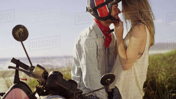 Affectionate young couple at motorcycle with beach in background Royalty-free stock photo