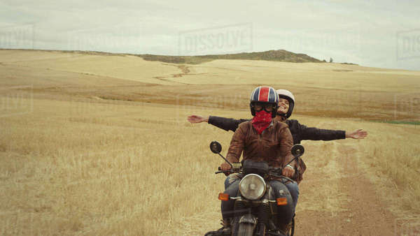 Exuberant young woman riding motorcycle in rural countryside Royalty-free stock photo