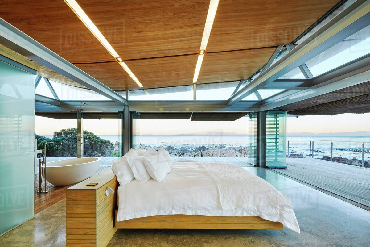 . Modern luxury bedroom open to patio with ocean view stock photo