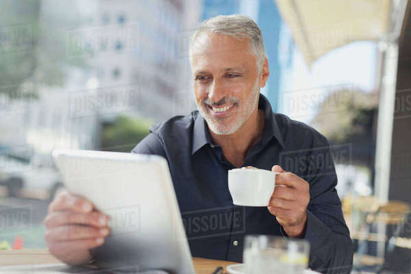 Smiling businessman using digital tablet drinking coffee at urban sidewalk cafe Royalty-free stock photo