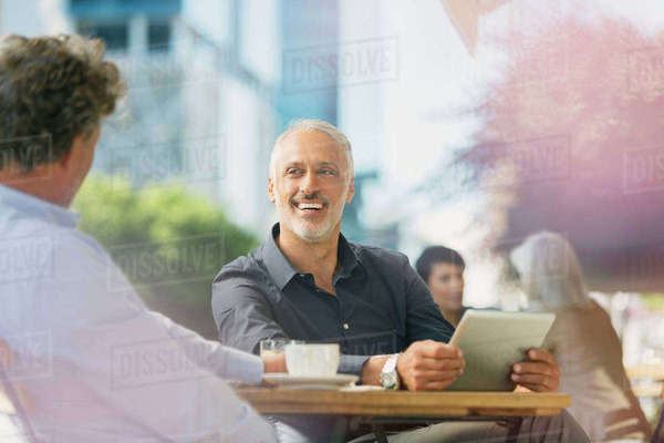 Smiling businessmen talking, drinking coffee and using digital tablet at sidewalk cafe Royalty-free stock photo
