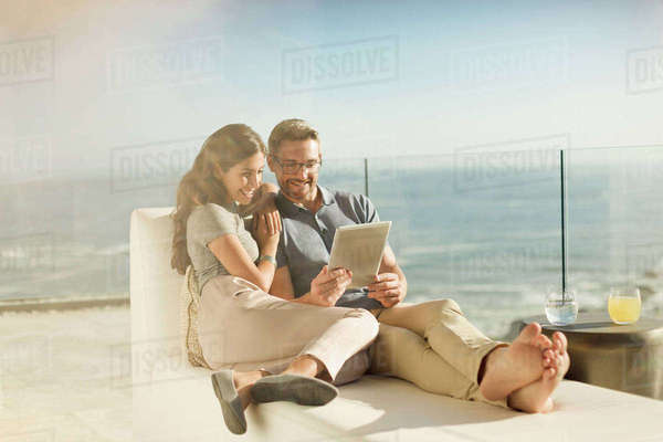Couple relaxing using digital tablet on sunny luxury balcony with ocean view Royalty-free stock photo