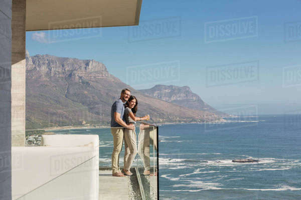 Couple looking at sunny ocean view from luxury balcony Royalty-free stock photo