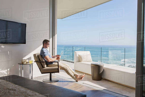 Man using digital tablet overlooking sunny ocean view Royalty-free stock photo