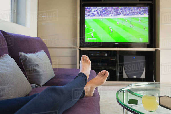 Personal perspective woman with bare feet up watching soccer game on TV in living room Royalty-free stock photo
