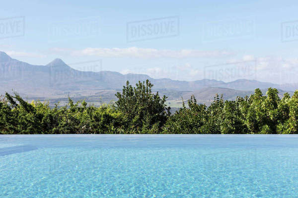 Tranquil luxury infinity pool with sunny mountain view Royalty-free stock photo
