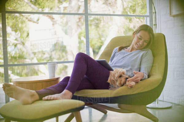 Woman with laptop relaxing and petting dog on chair Royalty-free stock photo