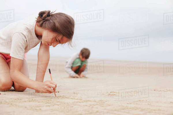 Girl with stick writing in sand on summer beach Royalty-free stock photo