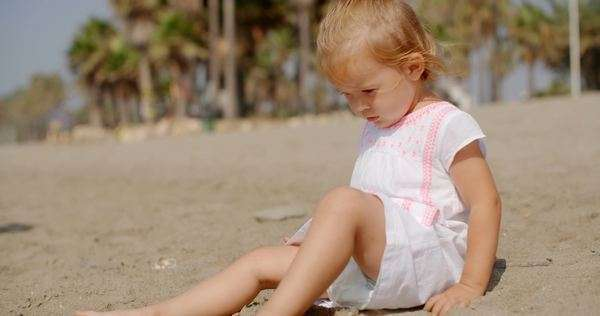 Cute young girl playing on sandy tropical beach in slow motion Royalty-free stock video