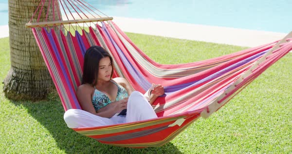 beautiful single young adult woman in bikini top and white pants seated  fortably in colorful hammock single smiling woman using laptop  puter in colorful hammock      rh   dissolve