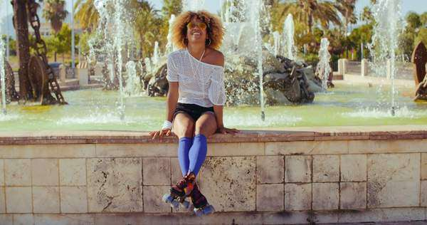 Slow motion video of happy sexy girl with afro haircut and sunglasses  sitting on fountains wall Royalty-free stock video