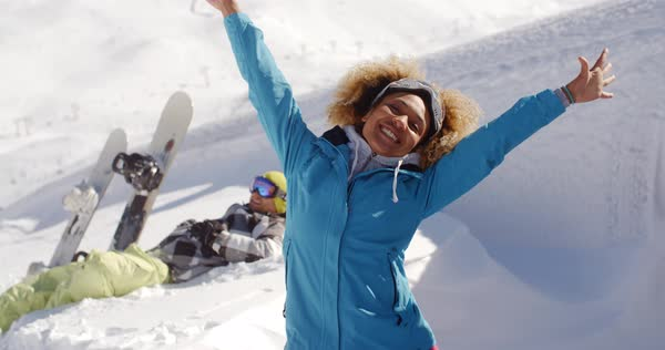 6ba96e1741 Successful young woman skier in blue jacket with rejoicing expression and  outstretched arms near man in