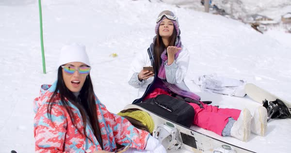 689efd1ad0 Two attractive women snowboarders relaxing sitting in the fresh snow at a  resort with their mobile