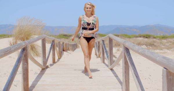 Full length shot of a happy young woman in swimming wear walking on the wooden beach pathway  Royalty-free stock video