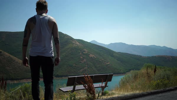 Wide shot of man approaching a bench overlooking a mountain lake Royalty-free stock video