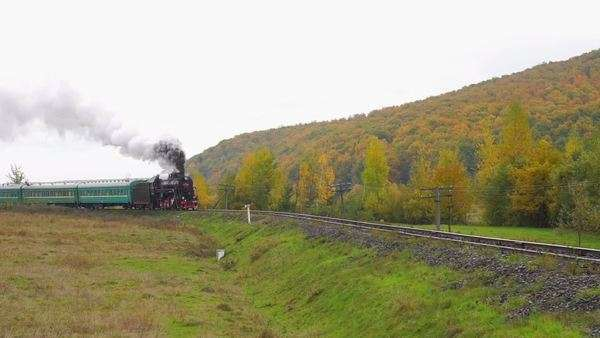 Old steam locomotive moves on rails between the hills Royalty-free stock video