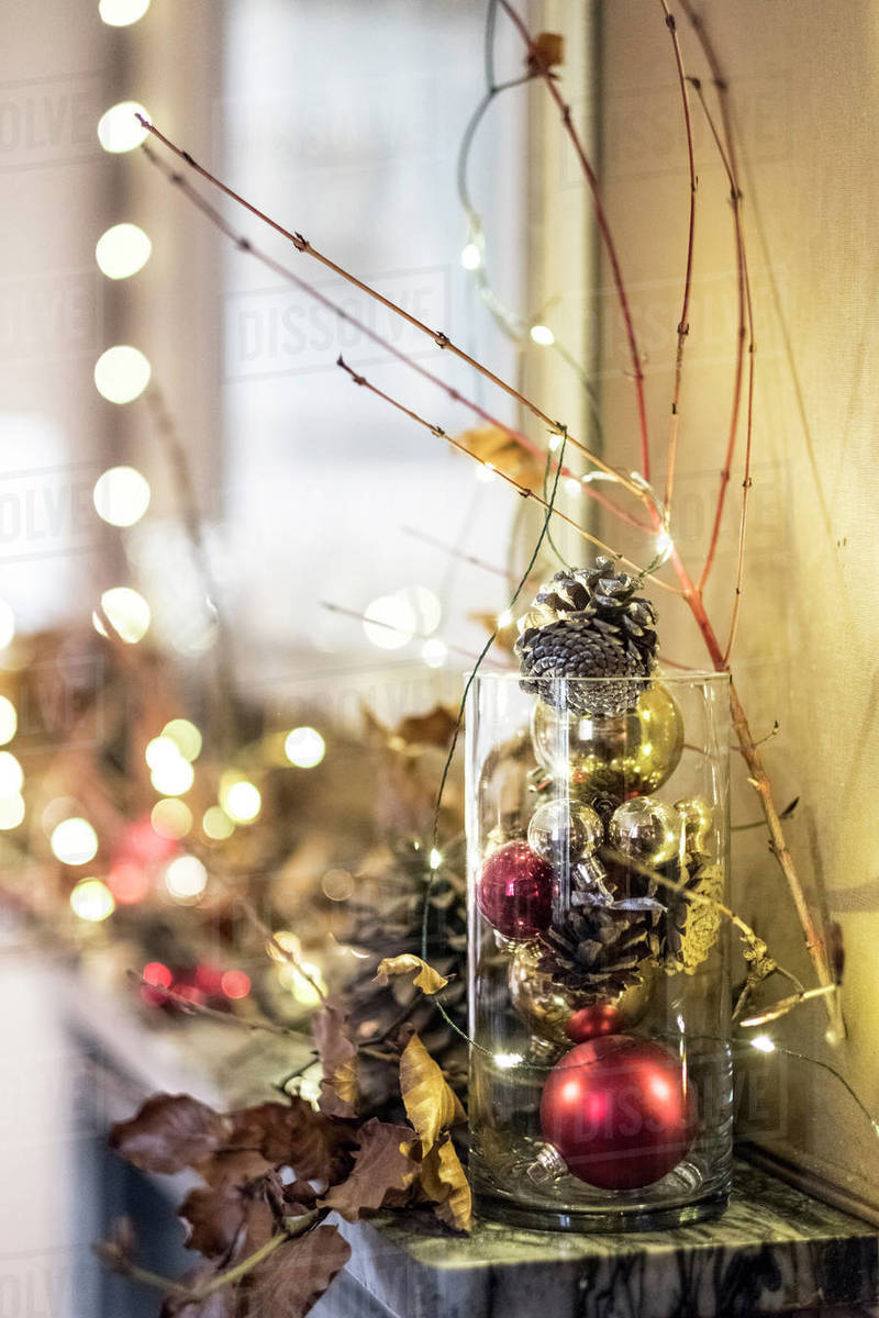 Close up of red and golden Christmas decorations in a vase, bauble, leaves and twigs.