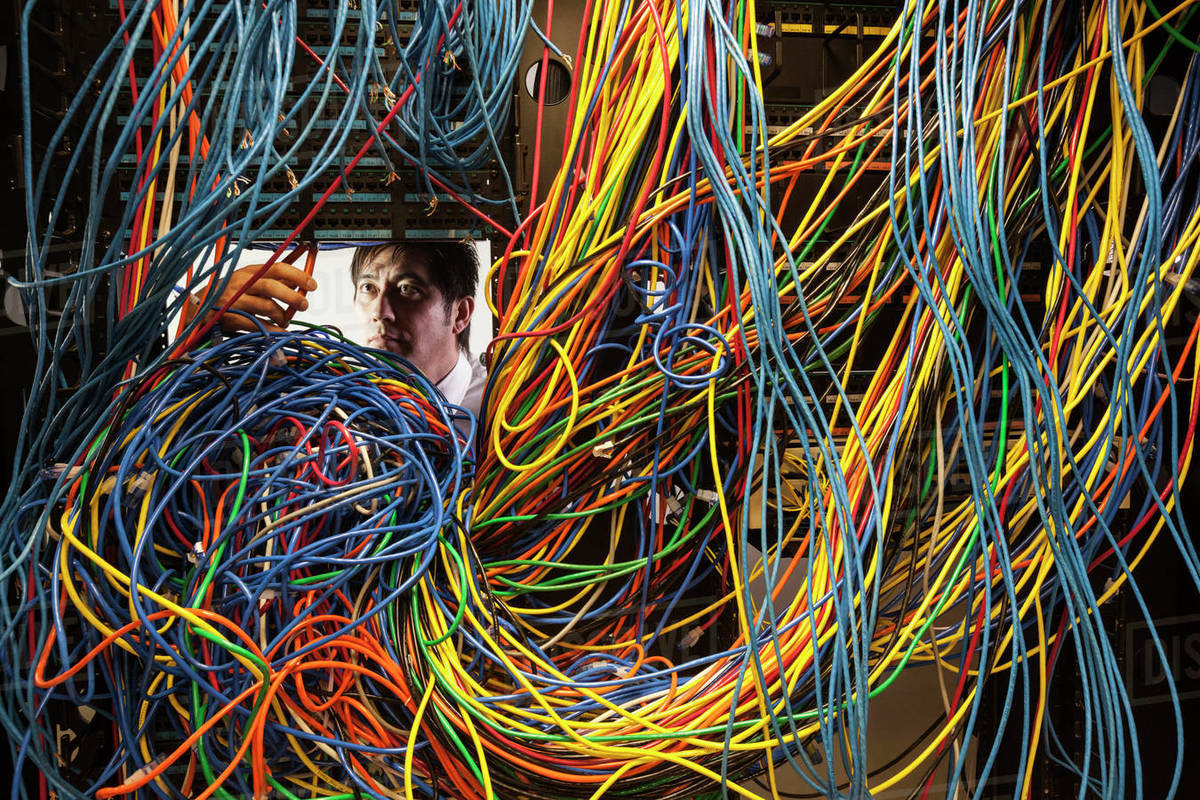Asian male technician working on a tangled mess of CAT 5 cables in a server  room  stock photo