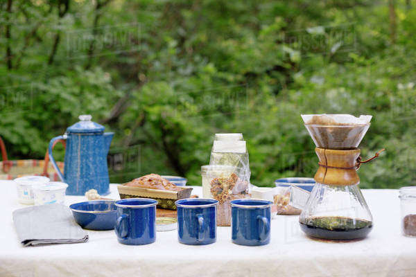 Table in a garden, with a coffee maker, mugs and bowls, a cake and cereal. Royalty-free stock photo