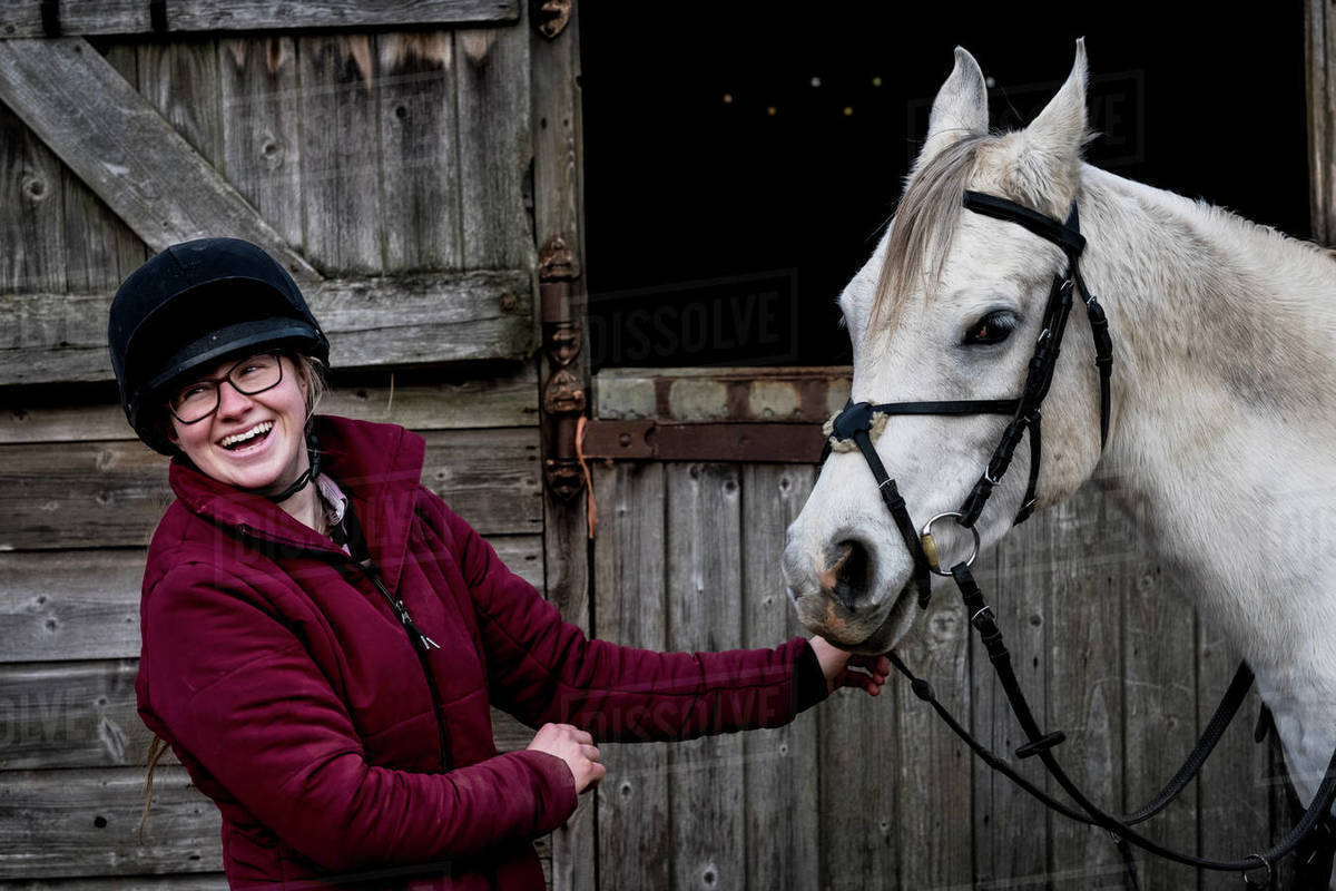 Young woman standing outside stable, holding white Cob horse by it's reins. Royalty-free stock photo