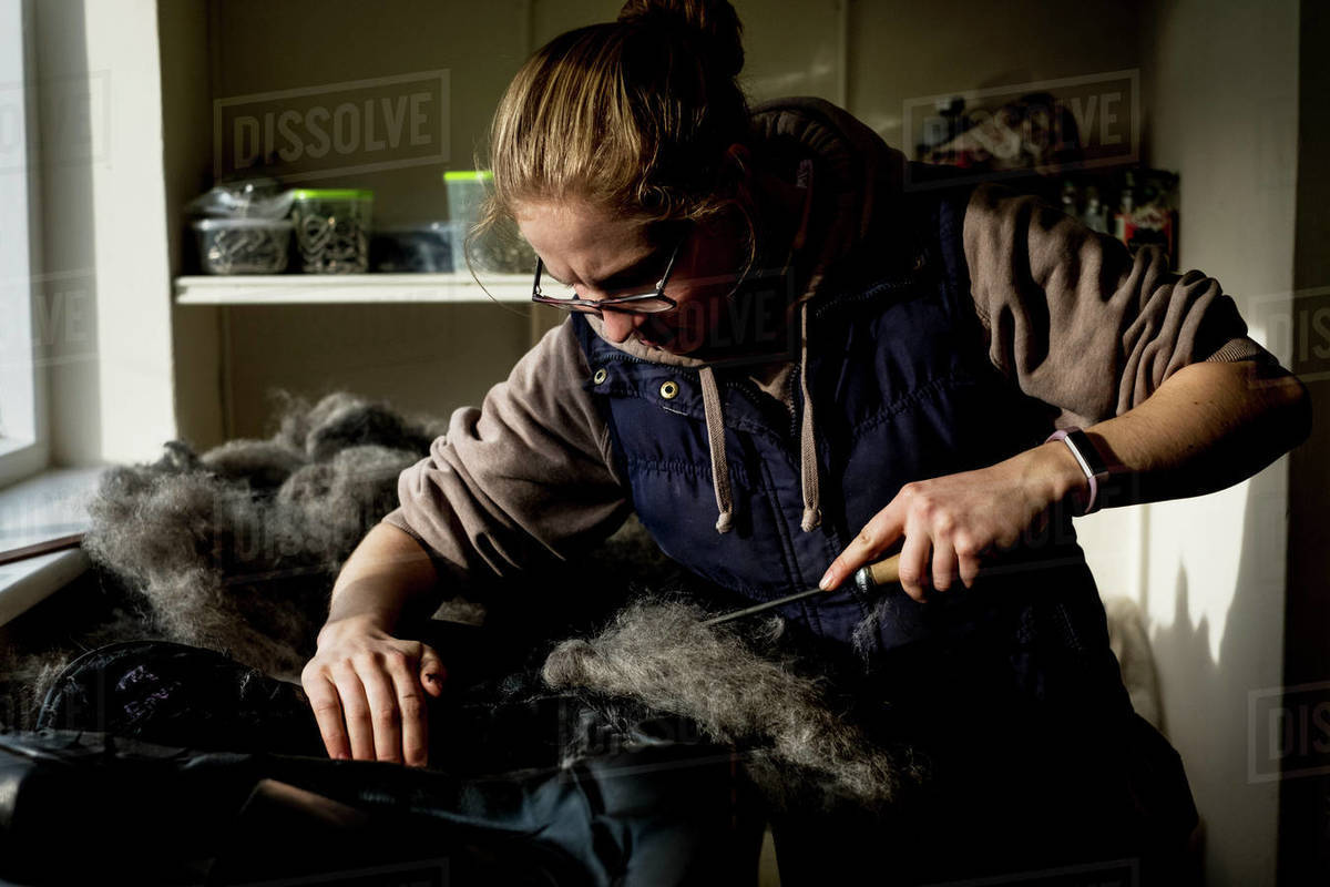 Female saddler standing in workshop, stuffing leather saddle with horse hair. Royalty-free stock photo