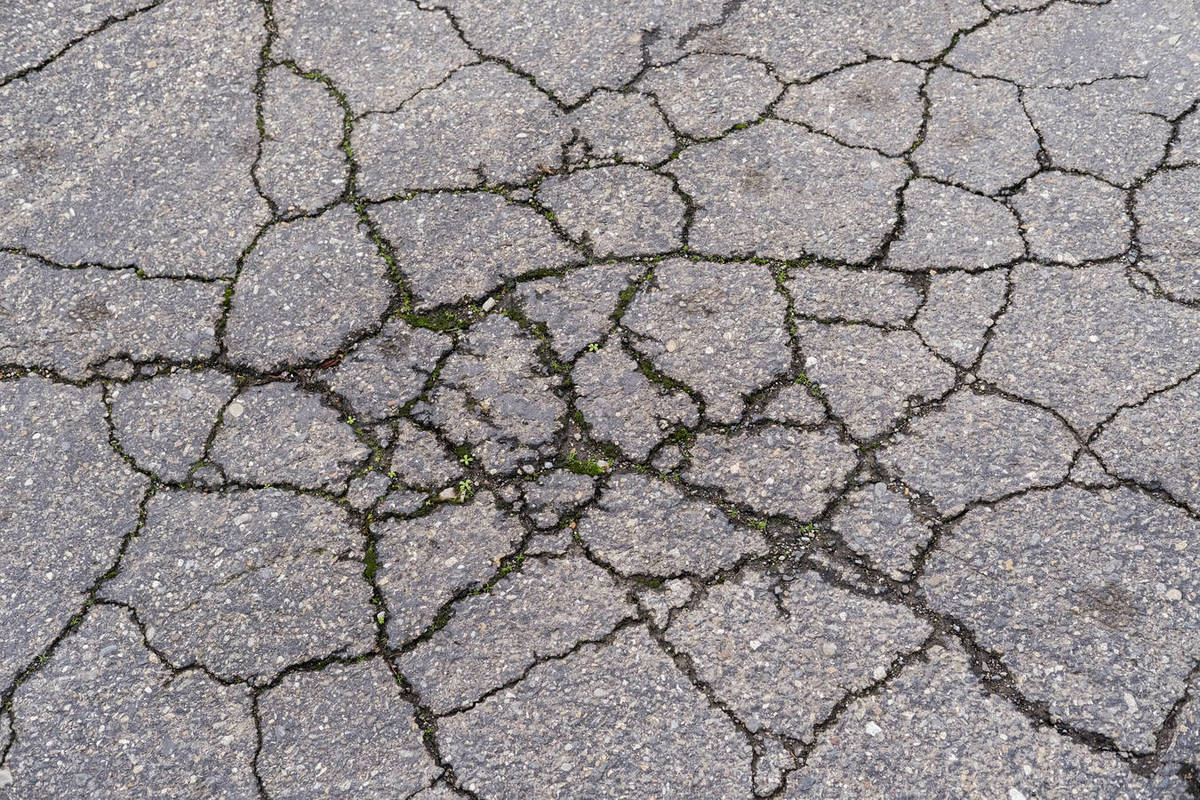 Detail of cracked and fractured asphalt road surface Royalty-free stock photo