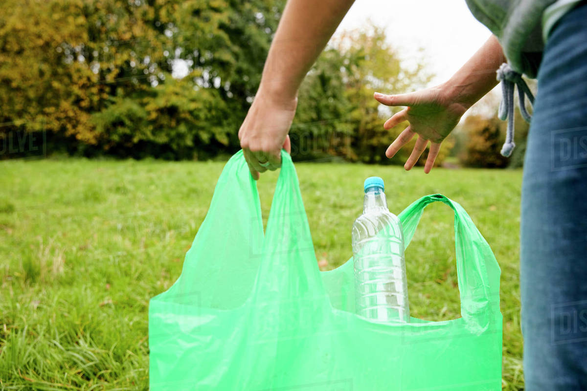 Woman stuffing soft waste plastics into large plastic bottle to make an ecobrick which can then be used as a buiding block Royalty-free stock photo