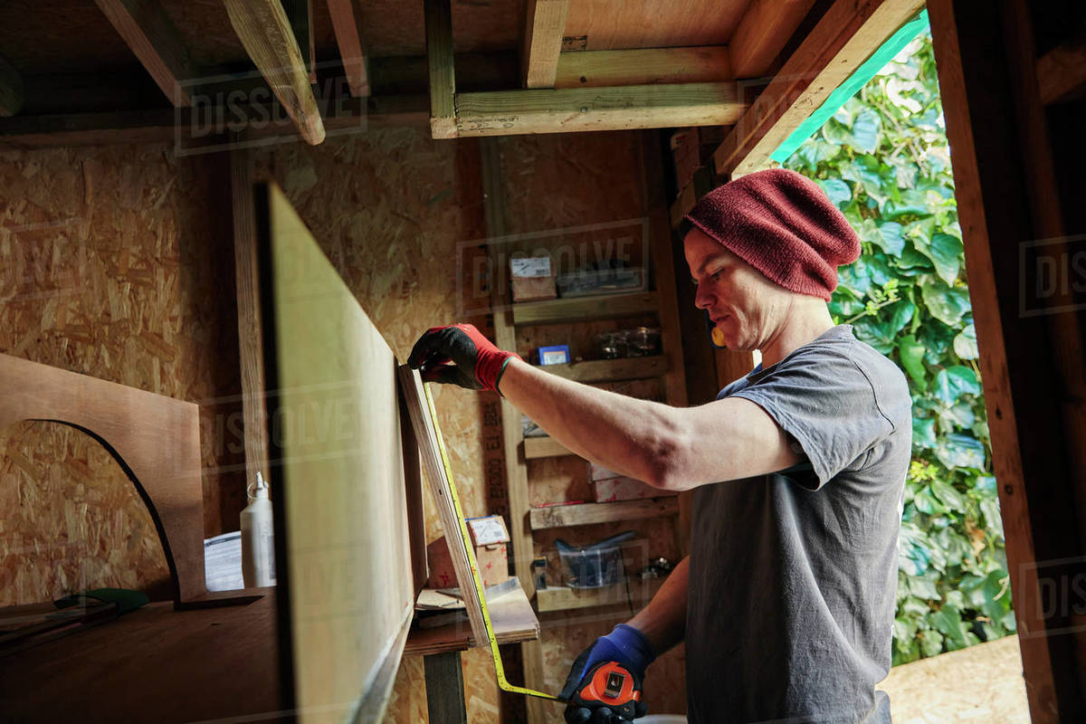 Carpenter using tape measure in shed Royalty-free stock photo