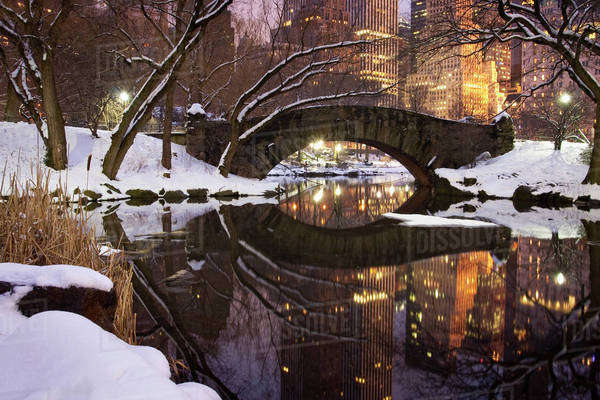 View across the Pond towards Gapstow Bridge in Central Park in Manhattan after a snow storm at dusk. Royalty-free stock photo