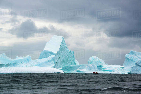Group of people crossing the ocean in the Antarctic in a rubber boat,  icebergs in the background. Royalty-free stock photo