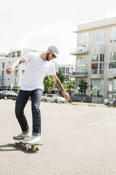 Young man skateboarding in a car park. Royalty-free stock photo