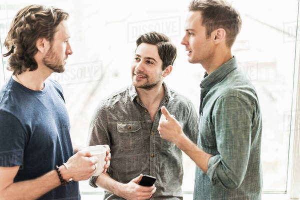 Three men standing talking, one with a cup of coffee, one with a smart phone. Royalty-free stock photo