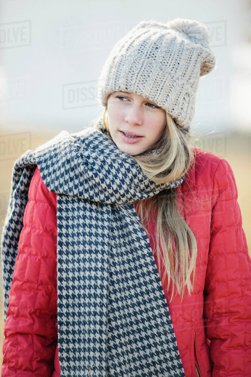 A girl in a red jacket with a large checked woollen scarf. Royalty-free stock photo