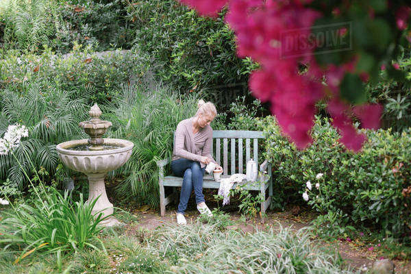 Woman sitting on a wooden bench in a garden, taking a break. Royalty-free stock photo