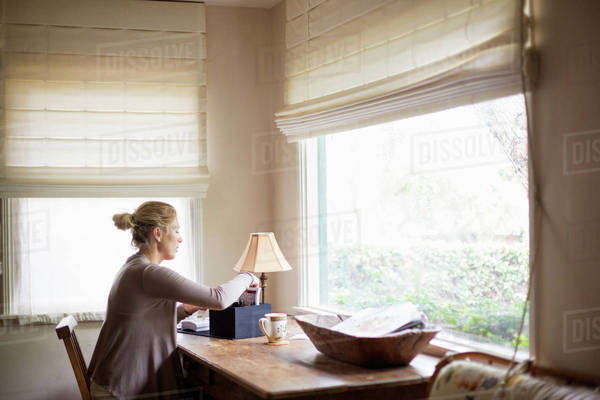 Blond woman sitting at a desk by a window, sorting through a box with photographs. Royalty-free stock photo