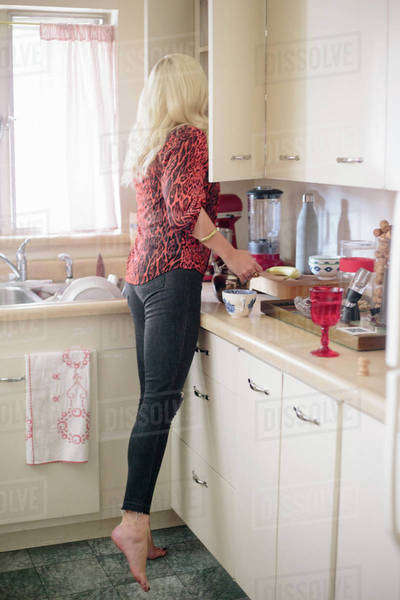 Blonde woman standing in a kitchen on tiptoes looking in a cupboard. Royalty-free stock photo