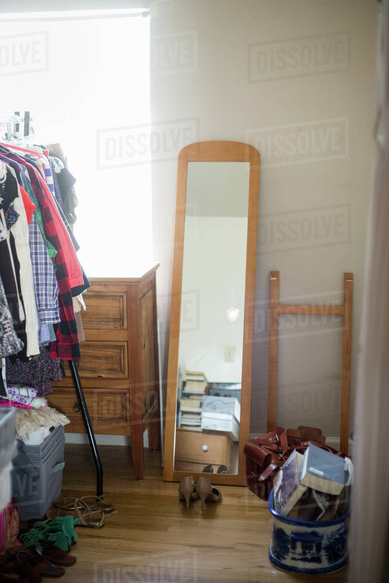 Mirror, chest of drawers, clothes rack and shoes in a bedroom. stock photo