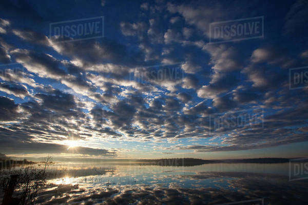 A dramatic cloud pattern across the sky and the sun setting over the waters of a lake.  Royalty-free stock photo