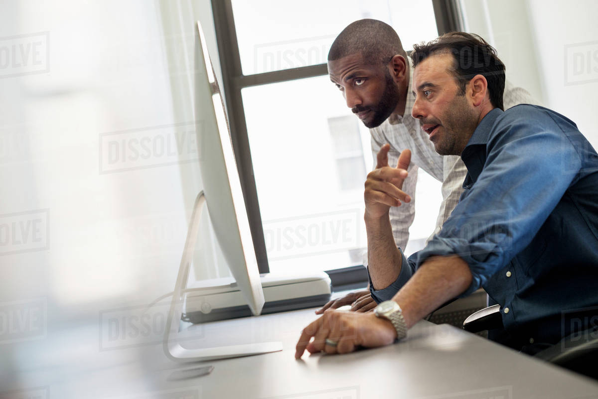 office life. two men at a desk looking at a computer. - stock photo