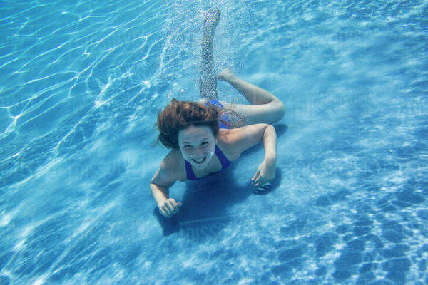 A young girl with long hair fanning out in the water, swimming underwater.  Royalty-free stock photo