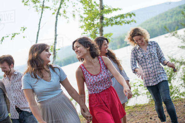 A group of people enjoying a leisurely walk by a lake. Royalty-free stock photo