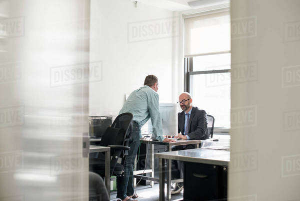 Office life. Two people talking to each other over a desk.  Royalty-free stock photo