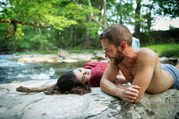 A young man and woman lying on the rocks on a river bank. Royalty-free stock photo