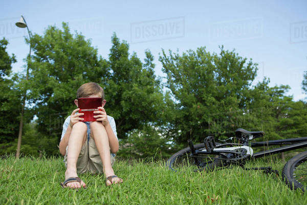 A young boy sitting on the grass playing a hand held electronic game.  Royalty-free stock photo