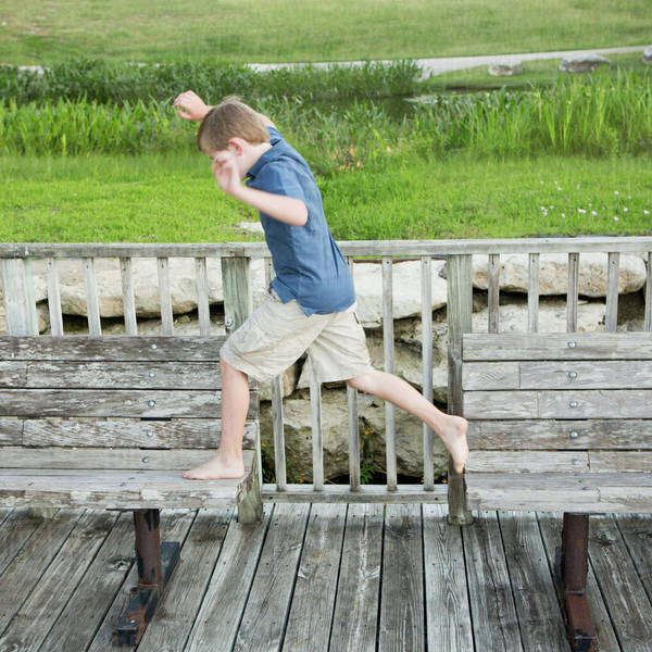 A young boy outdoors leaping from one bench to another on a jetty over water.  Royalty-free stock photo