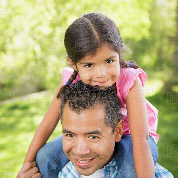 A man giving his daughter a piggyback ride on his shoulders. Royalty-free stock photo