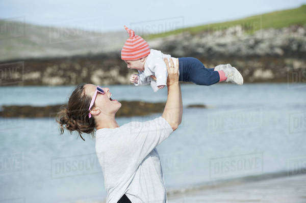 A mother raising her baby in the air. At the seaside. Royalty-free stock photo
